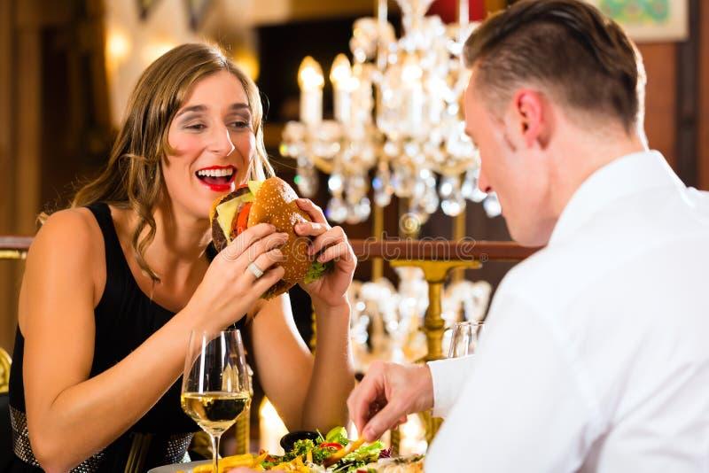 Os pares felizes no restaurante comem o fast food imagem de stock