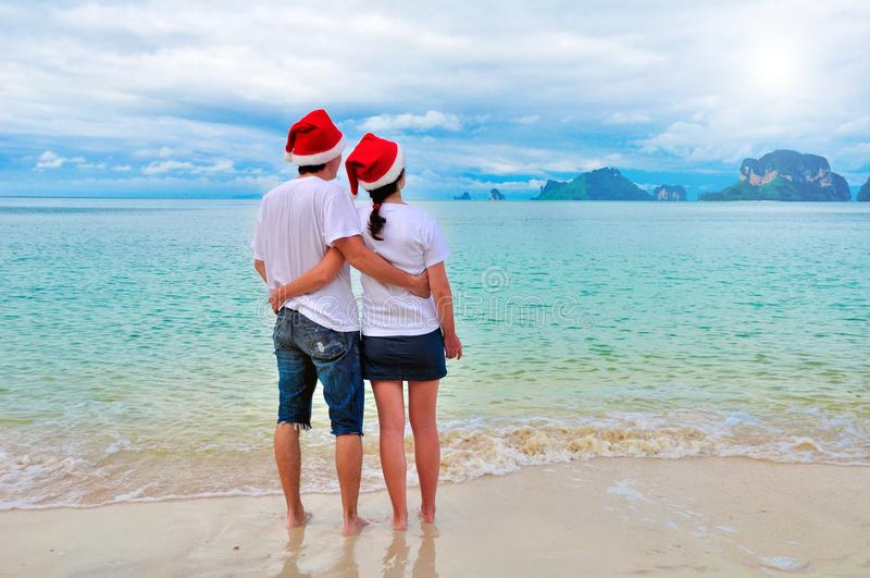 Os pares felizes nos chapéus de Santa que relaxam no Sandy Beach tropical perto do mar, do feriado do Natal e do ano novo vacatio fotos de stock royalty free