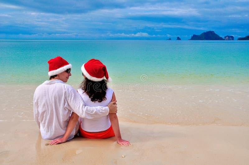 Os pares felizes nos chapéus de Santa que relaxam no Sandy Beach tropical perto do mar, do feriado do Natal e do ano novo vacatio imagem de stock royalty free
