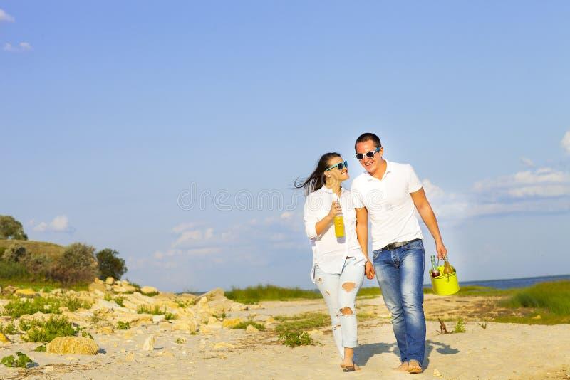 Os pares felizes novos no amor no verão tomam parte num piquenique imagens de stock royalty free