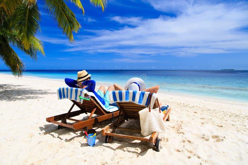 Os pares felizes relaxam em uma praia tropical imagem de stock royalty free