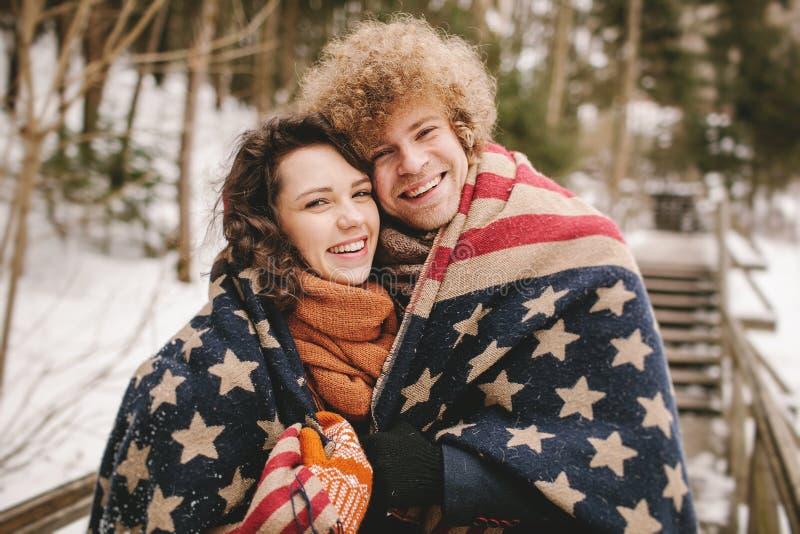 Os pares felizes sob o tapete da bandeira dos Estados Unidos no inverno estacionam imagem de stock