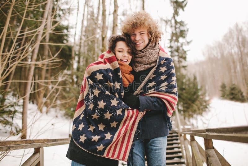 Os pares felizes sob o tapete da bandeira dos Estados Unidos no inverno estacionam imagem de stock royalty free