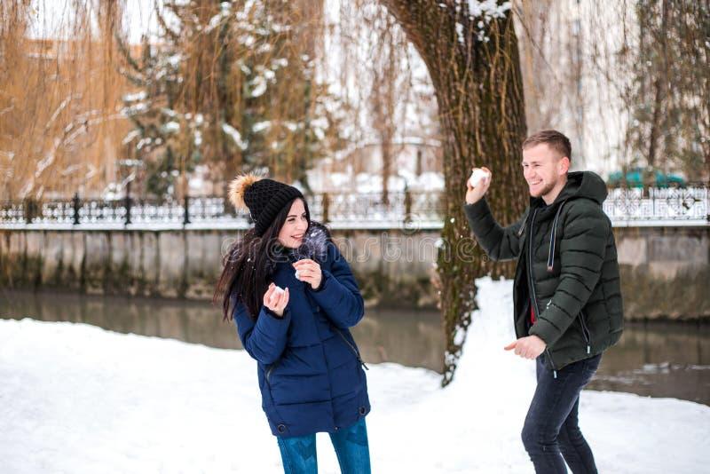 Os pares felizes têm o divertimento no parque do inverno fotos de stock royalty free