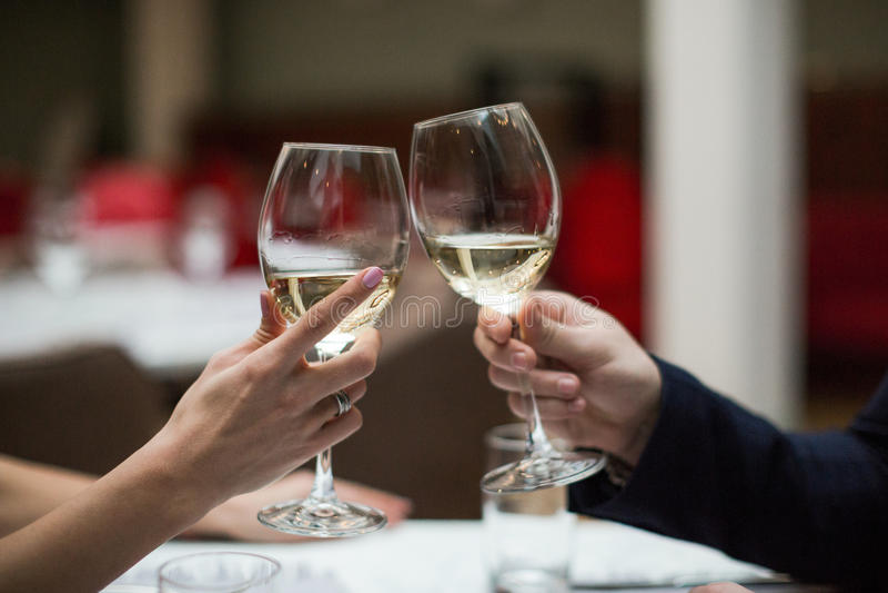 Os pares felizes têm uma data romântica em um restaurante que de jantar fino bebem vidros do vinho e do tinido imagens de stock