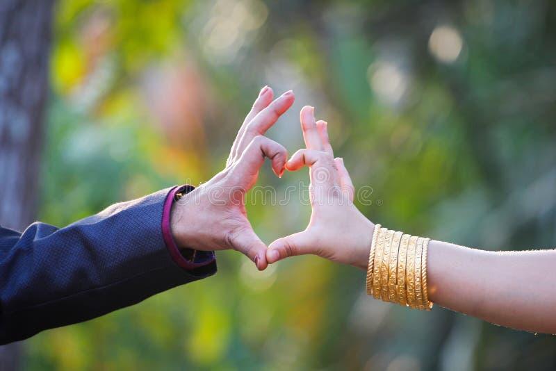 Os pares fizeram a forma do coração com dedos imagens de stock
