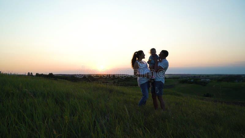 Os pares grávidos com filha da criança têm o tempo de lazer fora no por do sol imagens de stock royalty free