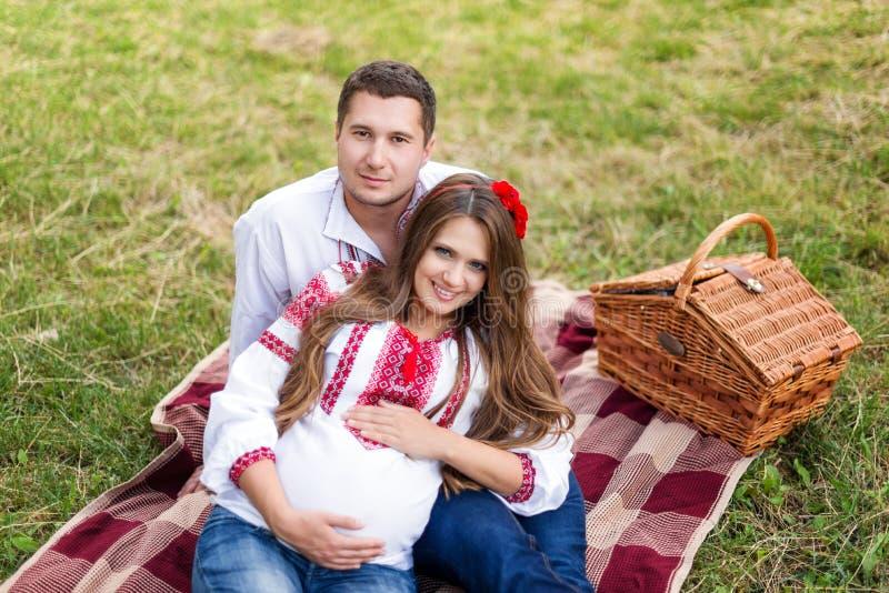 Os pares grávidos novos bonitos vestiram-se no estilo ucraniano nacional que tem o piquenique no parque do outono Maternidade e h imagens de stock