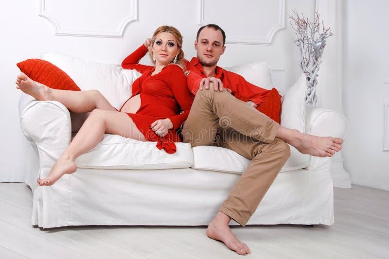 Os pares grávidos novos felizes vestiram-se no abraço vermelho fotografia de stock