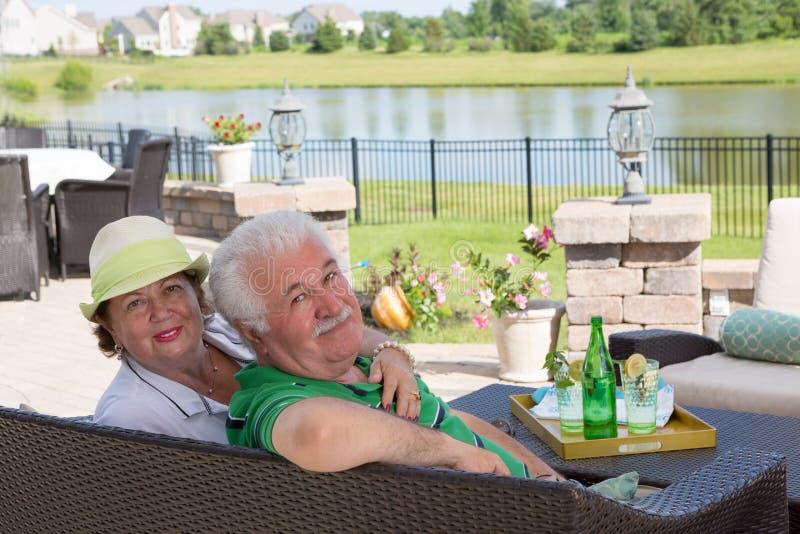 Os pares idosos apreciam um dia de relaxamento no pátio imagem de stock