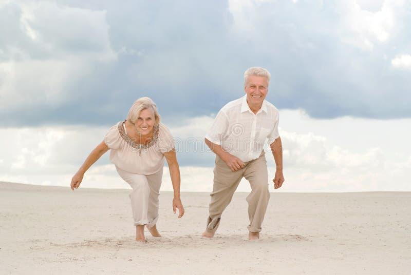 Os pares idosos encantadores apreciam a brisa de mar fotografia de stock royalty free