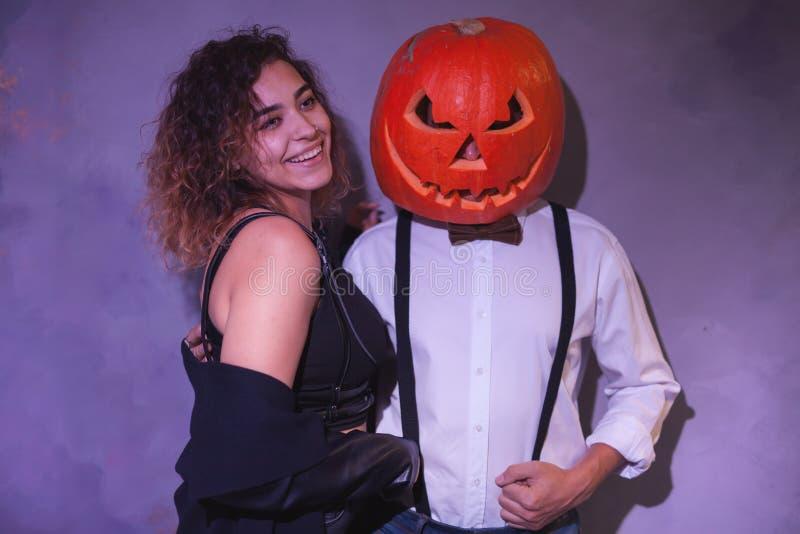 Os pares incomuns em Dia das Bruxas party, mulher com a abóbora na cabeça imagem de stock royalty free