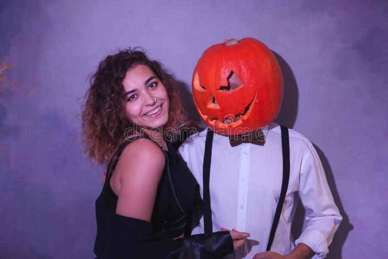 Os pares incomuns em Dia das Bruxas party, mulher com a abóbora na cabeça foto de stock royalty free