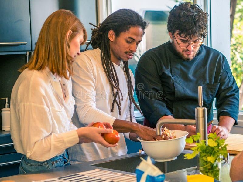 Os pares inter-raciais de marido africano e de esposa caucasiano preparam o alimento junto com um cozinheiro chefe profissional imagem de stock royalty free
