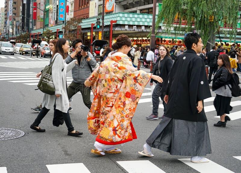 Os pares japoneses bonitos novos vestiram-se em trajes japoneses nacionais e fotografaram-se no Tóquio da cidade da rua, Japão imagens de stock