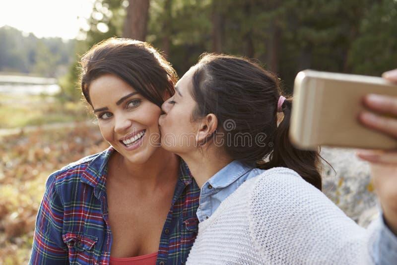 Os pares lésbicas no campo beijam e tomam um selfie imagens de stock