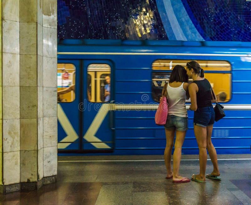 Os pares lésbicas que estão na estação subterrânea no fundo da equitação treinam imagem de stock