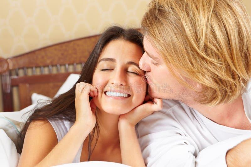 Os pares levantam na cama imagens de stock royalty free