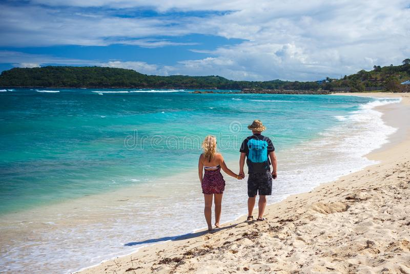 Os pares loving de viajantes que guardam as mãos andam em uma praia das caraíbas imagens de stock royalty free
