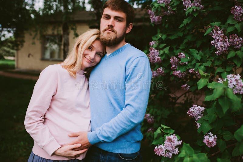 Os pares loving felizes com a mulher gravida que anda na mola estacionam foto de stock