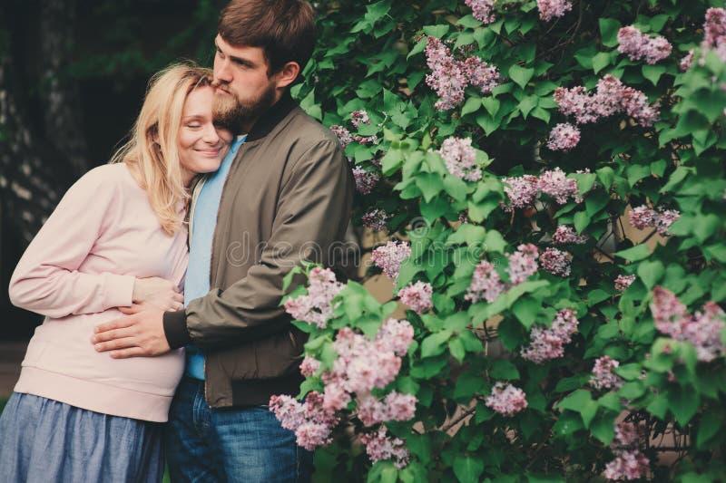 Os pares loving felizes com a mulher gravida que anda na mola estacionam fotos de stock royalty free