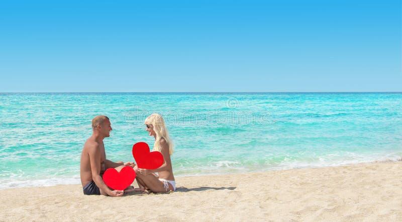 Os pares loving no mar arenoso encalham com corações vermelhos - Valentim do St fotos de stock