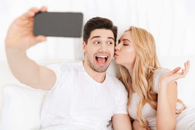 Os pares loving novos bonitos fazem o selfie fotos de stock