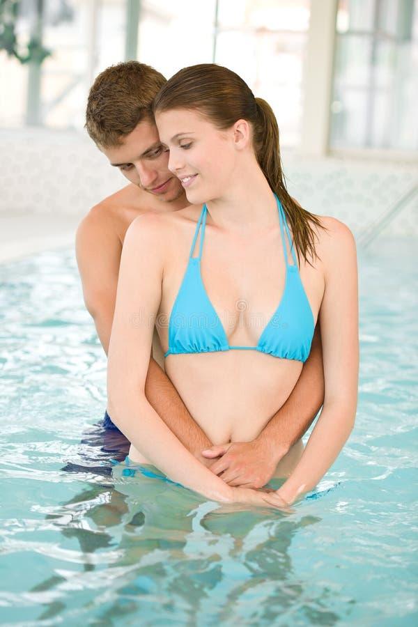 Os pares loving novos relaxam na piscina fotografia de stock
