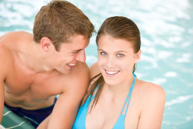Os pares loving novos têm o divertimento na piscina imagens de stock