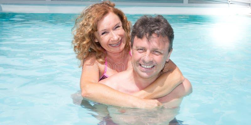 Os pares maduros estão relaxando na piscina em férias de verão imagens de stock