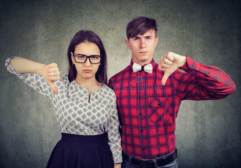 Os pares mal-humorados infelizes que dão os polegares para baixo gesticulam, discordam com o algo fotografia de stock royalty free