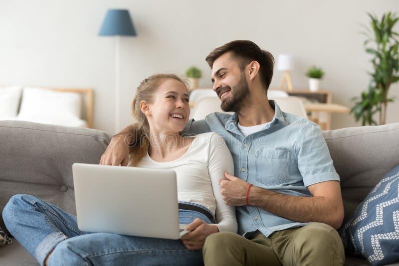Os pares milenares felizes passam o fim de semana em casa junto imagem de stock royalty free