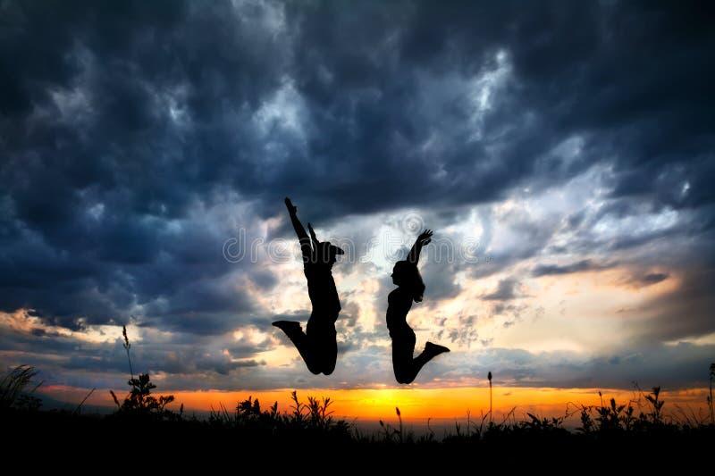 Os pares mostram em silhueta o salto no por do sol foto de stock royalty free