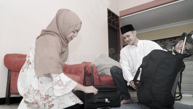 Os pares muçulmanos puseram o material no lugage da mala de viagem pronto para viajar fotografia de stock royalty free