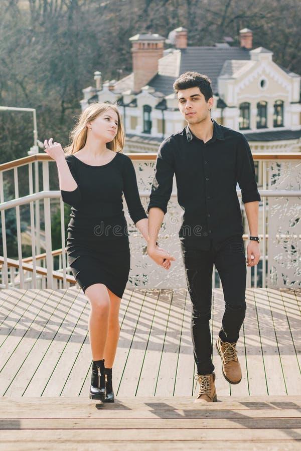 Os pares multirraciais novos bonitos, um par estudantes andam nas escadas em Kiev no centro da cidade Morena turca consider?vel fotografia de stock