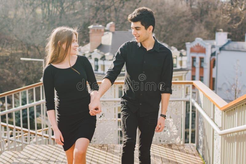 Os pares multirraciais novos bonitos, um par estudantes andam nas escadas em Kiev no centro da cidade Morena turca consider?vel fotos de stock