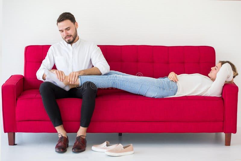 os pares na amiga do amor que encontra-se para baixo no noivo vermelho do sofá fazem massagens seus pés em casa, dentro imagem de stock royalty free
