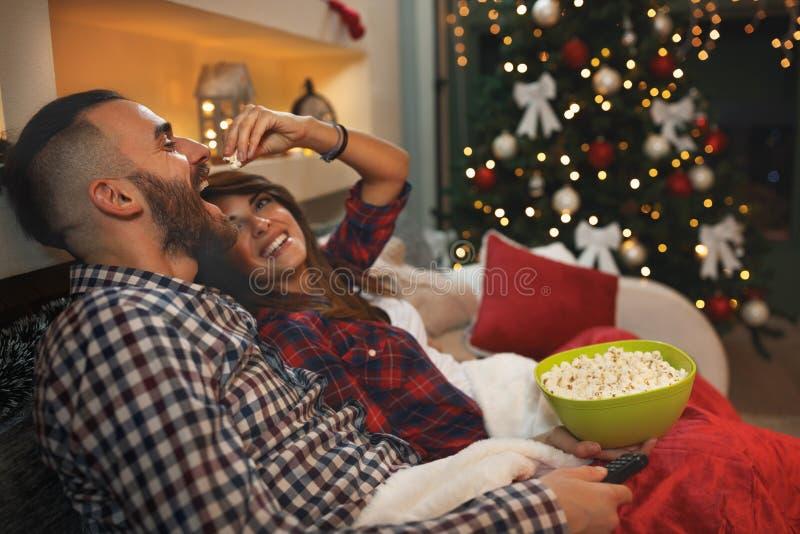 Os pares na Noite de Natal apreciam com pipoca ao olhar a tevê foto de stock