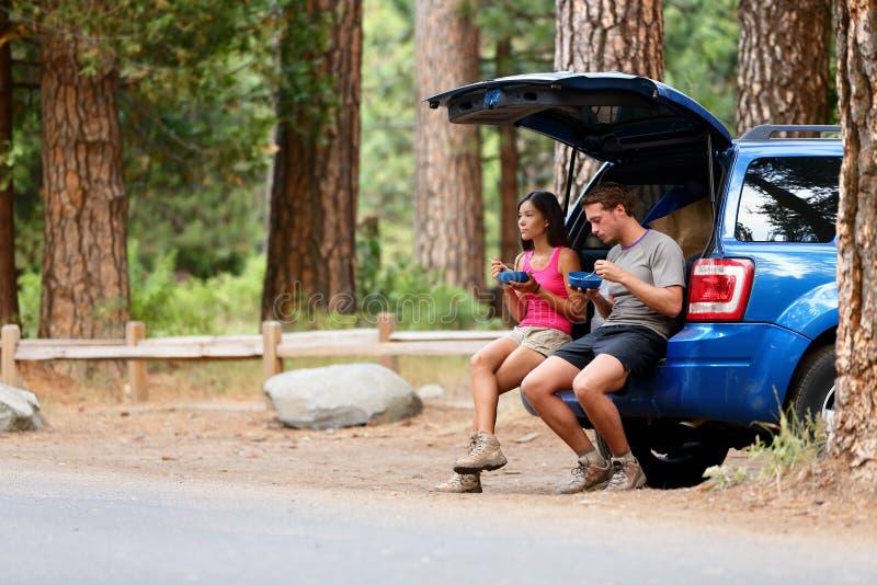 Os pares na viagem por estrada do carro viajam em comer na floresta fotografia de stock royalty free