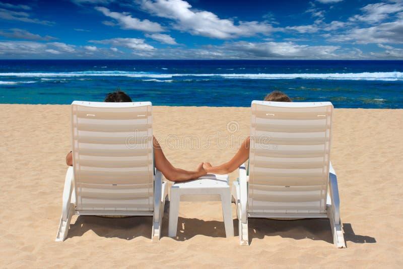 Os pares nas cadeiras de praia que prendem as mãos aproximam o oceano fotografia de stock