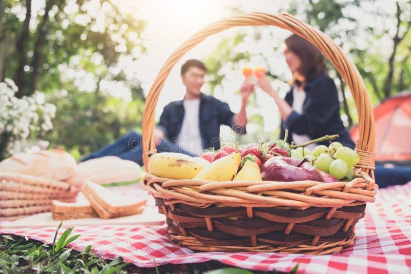 Os pares no amor bebem um suco de laranja e os frutos no verão tomam parte num piquenique, lazer, feriados, comer, povos e concei imagem de stock royalty free