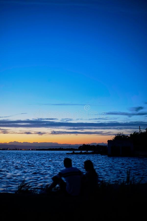 Os pares no amor contemplam o por do sol no Albufera de Valência fotos de stock
