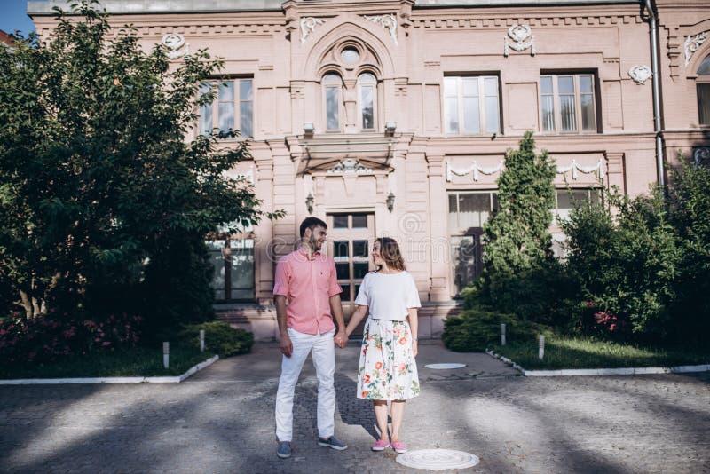 Os pares no amor estão na cidade velha Construção velha e árvores verdes no fundo Pares que guardam as mãos e que olham se fotos de stock royalty free