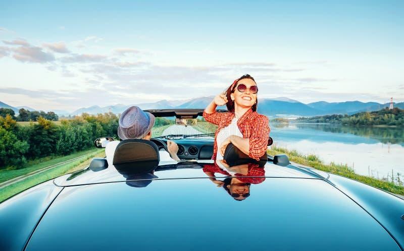 Os pares no amor montam no cabriolet na montanha pitoresca roa foto de stock royalty free