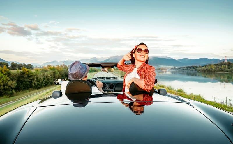 Os pares no amor montam no cabriolet na montanha pitoresca roa imagens de stock royalty free