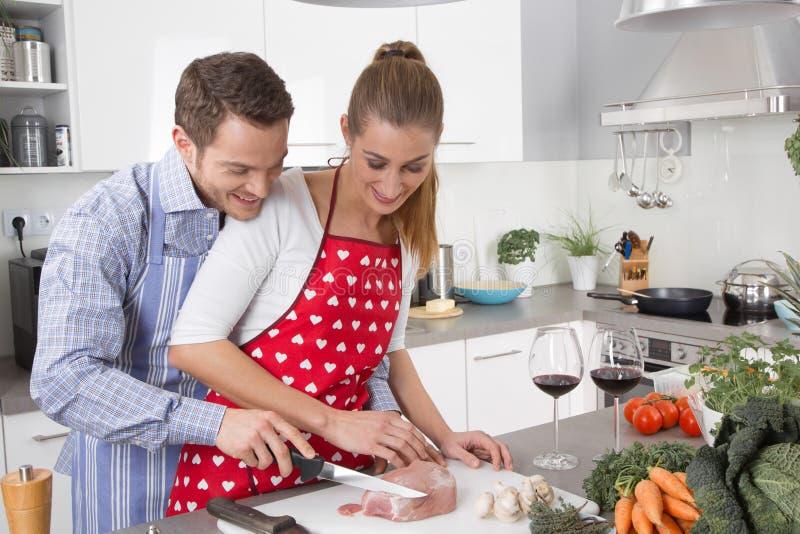 Os pares no amor que cozinha junto na cozinha e têm o divertimento imagens de stock