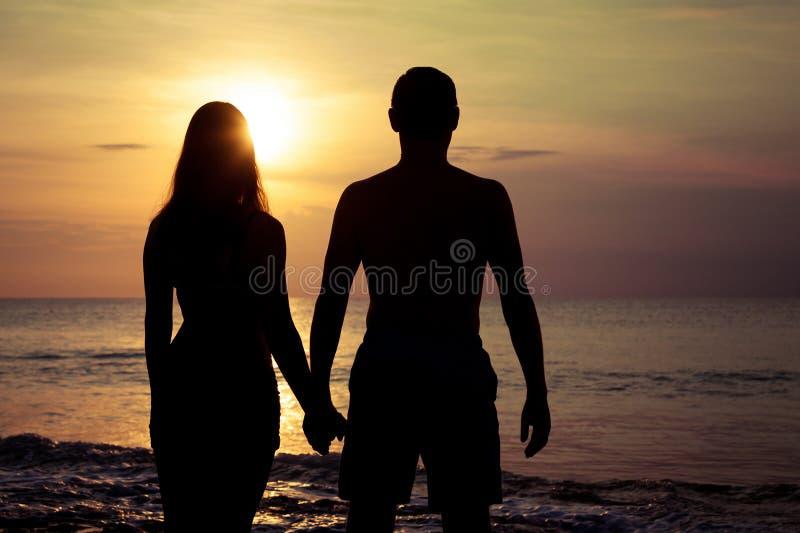 Os pares no amor suportam a silhueta clara no mar imagens de stock royalty free