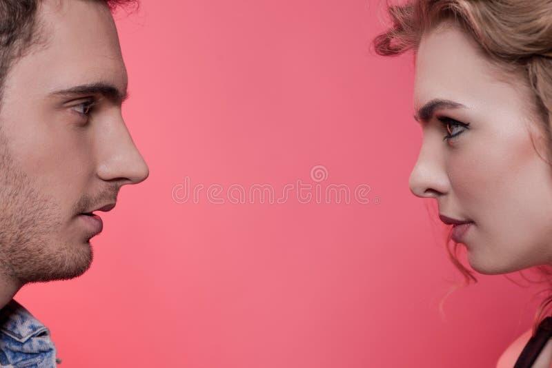 Os pares novos à moda no amor que olha se isolaram-se no rosa imagem de stock