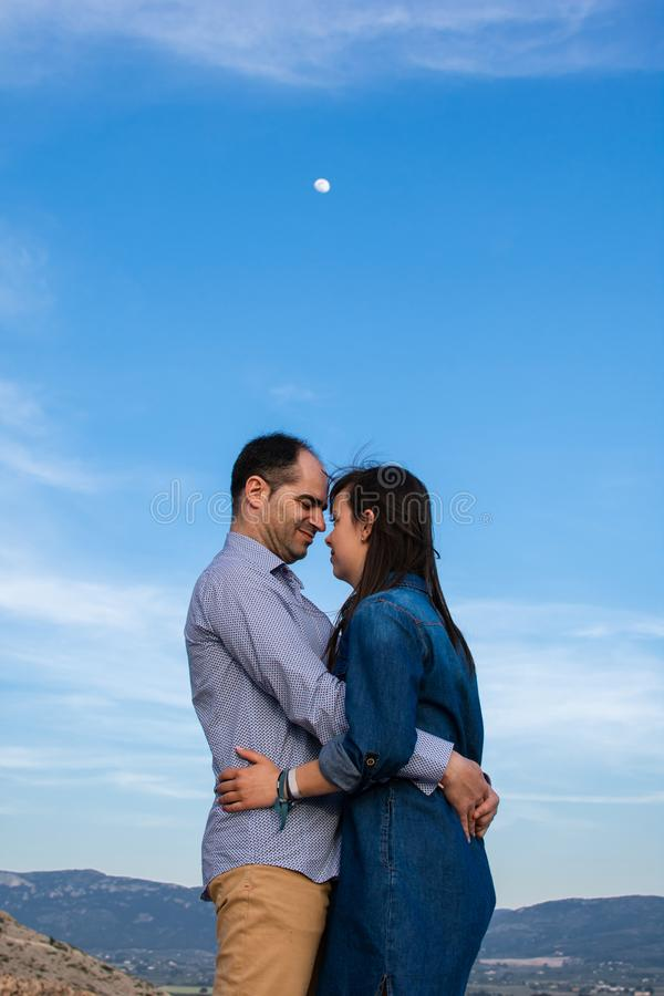 Os pares novos abraçaram com a lua no fundo fotografia de stock