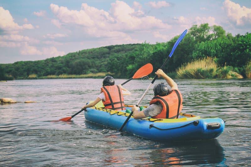 Os pares novos apreciam a ?gua branca que kayaking no rio imagens de stock royalty free